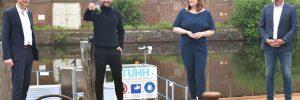 TU-Präsident Andreas Timm-Giel, Forscher Leonard Francke, Wissenschaftssenatorin Katharina Fegebank und Projektinitiator Sönke Knutzen vor dem Mikroalgenreaktor im Ziegelwiesenkanal am Hamburg Innovation Port.